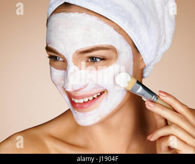 Woman with soothing facial mask. Close up of young woman on beige background. Beauty procedures skin care concept - Stock Photo