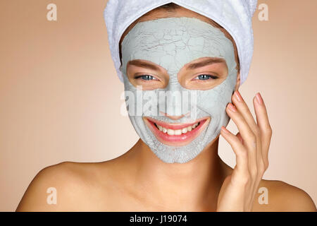 Laughing girl with clay facial mask. Happy young woman smiling enjoying spa treatments. Beauty & Skin care concept - Stock Photo