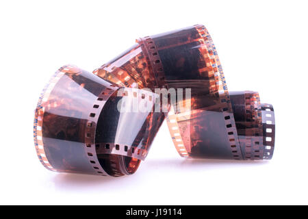 picture of curled color 35mm film against bright white background - Stock Photo