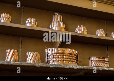 Collection of shiny vintage, antique metallic copper jelly mounds and other utensils displayed lined up on a shelf - Stock Photo