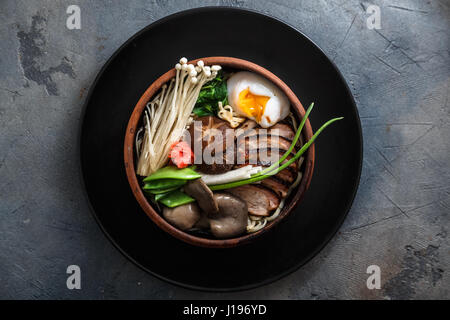 Ramen noodles with duck, egg, enoki and shiitake mushrooms with broth on dark background - Stock Photo