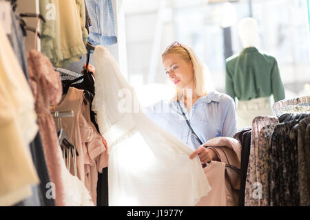 Beautiful woman shopping fashionable clothes in clothing store. - Stock Photo