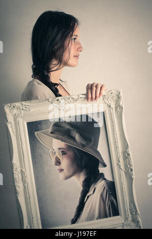 Woman holding framed picture of herself - Stock Photo