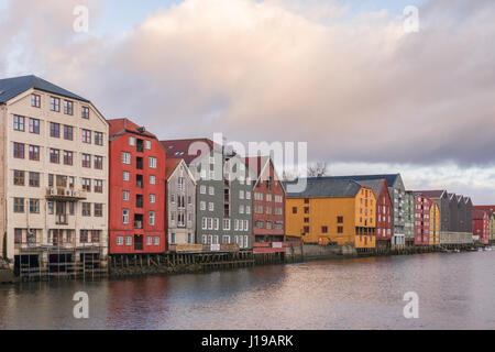 Traditional warehouses line the sides of the Nidelva River as it flows through Trondheim, Norway. - Stock Photo