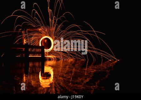 Spinning steel wool on bridge over a lake. Taken with Nikon D3200 - Stock Photo