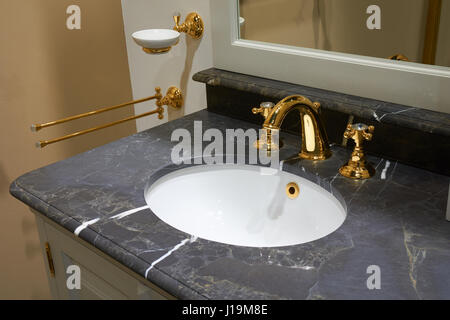 White inset ceramic washbasin in stone table and gold plated glossy metal mixer with crystals - Stock Photo