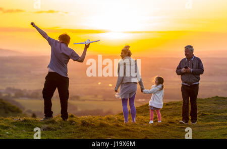 Family in the countryside in the evening in Spring, as the sun sets, throwing a toy plane and enjoying the sunset. - Stock Photo