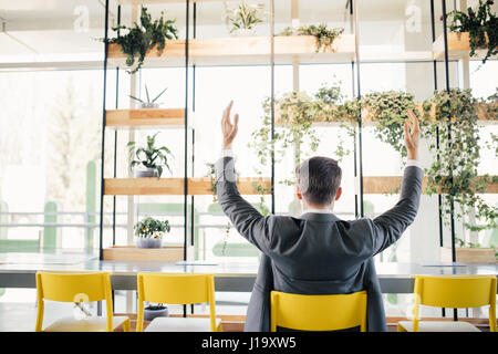 Successful business man happy smile hold fist gesture view from back, handsome young businessman with raised hands - Stock Photo