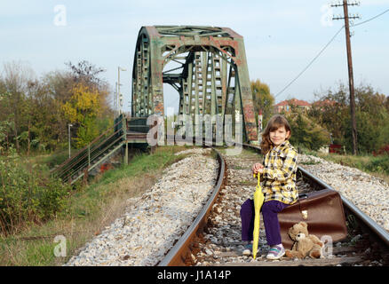 beautiful little girl sitting on suitcase - Stock Photo