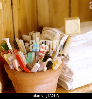 Pot of toothbrushes and pile of towels. - Stock Photo