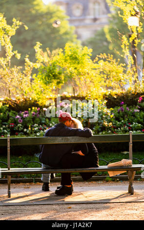 Couple kissing on park bench. - Stock Photo