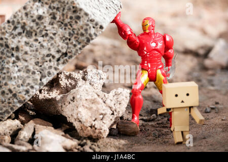 A Danbo Danboard character running away from falling masonary which is being held in place by a toy Iro Man character - Stock Photo