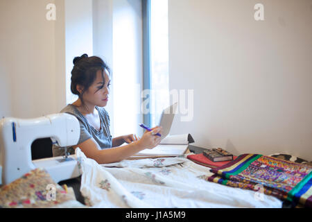 Young woman working on a tablet PC - Stock Photo