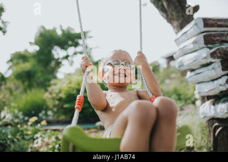 young coloured boy is having fun on the swing - Stock Photo