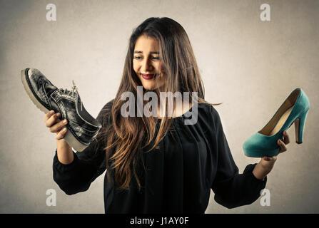 Woman choosing between flat and high heeled shoe - Stock Photo