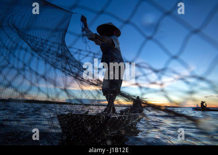 Thai fisherman on wooden boat casting a net for catching freshwater fish in nature river in the early evening before - Stock Photo