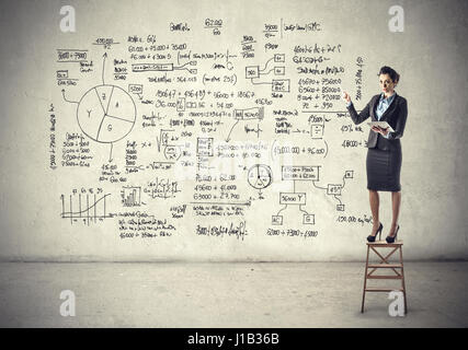 Businesswoman showing her plan on wall - Stock Photo