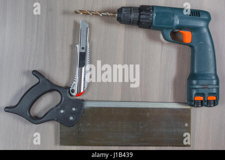 Different tools on a wooden background. Drill, knife, saw - Stock Photo