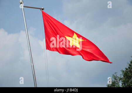 The vietnamese flag flying from a flag pole against the sky in the ben Douc scenic area in south vietnam. - Stock Photo