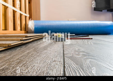 Laminate flooring and the tools required to lay it during DIY - pencil, square, hammer and pulling bar. Do it yourself. - Stock Photo