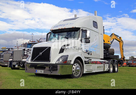 ALAHARMA, FINLAND - AUGUST 12, 2016: White Volvo VNL 64T 670 year 2004 with small excavator and other conventional - Stock Photo
