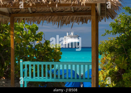 Shadey bench seat overlooking turqoise waters of Halfmoon Cay and Holland American Cruise Liner 'Amsterdam,' Bahamas - Stock Photo