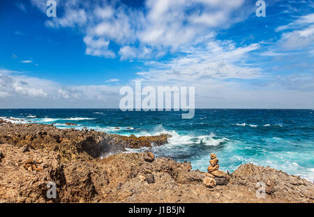 Aruba's windy, rocky north shore with rough seas even on a sunny Spring day - Stock Photo