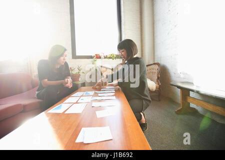 Women examining paperwork on coffee table - Stock Photo
