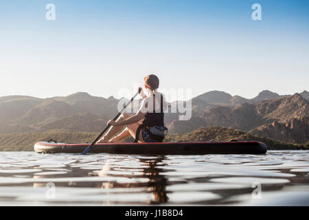 Caucasian woman sitting on paddleboard in river - Stock Photo