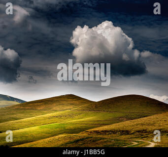Select all passed  landscape with green hills and dark clouds - Stock Photo