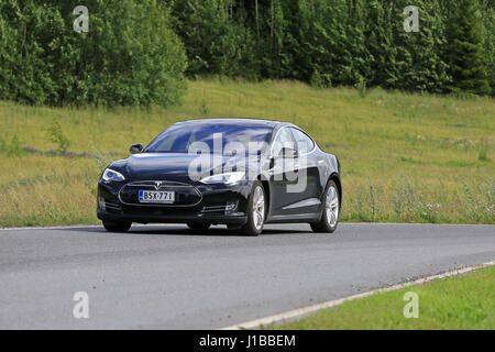PAIMIO, FINLAND - JULY 17, 2016: Black Tesla Model S electric vehicle moves on rural road through green Finnish - Stock Photo