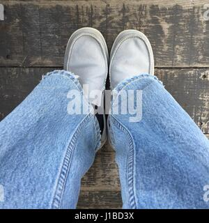 Young man wearing gray shoes and blue pants on wooden background great for any use. - Stock Photo