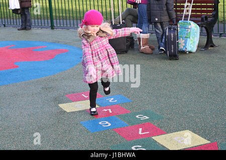 Little girl, child playing hopscotch in the playground in Stephen's Green Dublin Ireland kids playing playground - Stock Photo