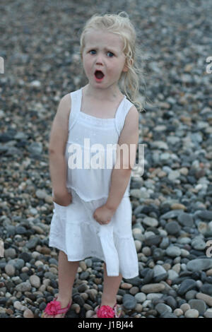 Little girl child having a tantrum on a stony beach - Stock Photo