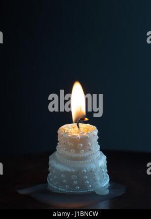 A burning, melting wedding cake candle. - Stock Photo