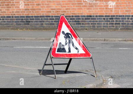 Battered portable sign warning of roadworks - Stock Photo