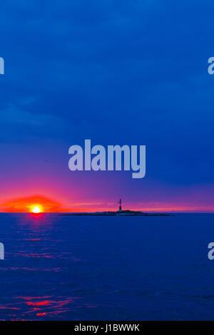 Sunset at sea lighthouse silhouette small tiny island before Porec in Croatia - Stock Photo