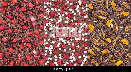 Three kinds of chocolate bars with dried berries, fruit, and nuts. Could be used as backgrounds. - Stock Photo