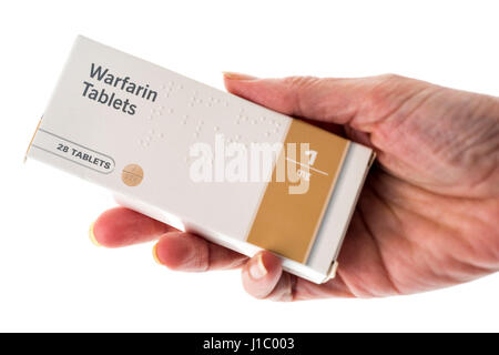 Female hand holding packet of Warfarin tablets - Stock Photo