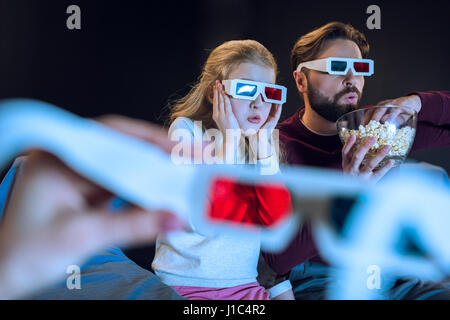 Shocked father and daughter in 3d glasses watching movie and eating popcorn - Stock Photo