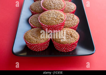 Bran muffins in bright red and white paper holders on a black rectangular plate and red background - Stock Photo