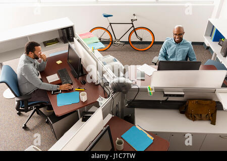Men working at computers in office - Stock Photo