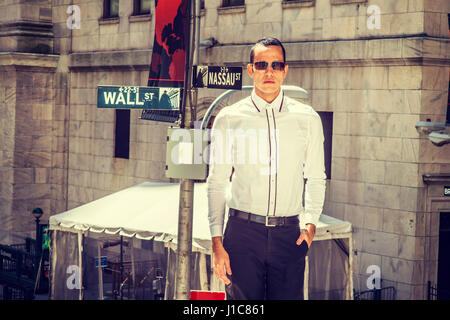 Young American Businessman traveling, working in New York, wearing white shirt, black pants, sunglasses, standing - Stock Photo
