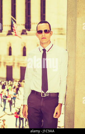 Young American Businessman traveling, working in New York, wearing white shirt, black tie, sunglasses, standing - Stock Photo