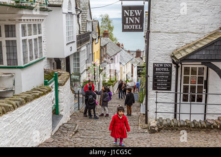 Clovelly,North Devon,England,UK. Visitors and tourists enjoy the steep and picturesque cottages, cobbled high street - Stock Photo