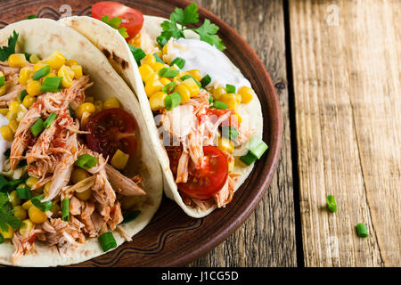 ... Homemade slow cooker chicken taco with corn served on rustic ceramic plate on wooden table & Mexican taco served on a white plate in Homemade Mexican restaurant ...