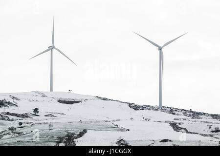 Horizontal outdoors shot of the two windmills placed on the hill in the winter - Stock Photo
