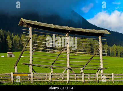 Traditional single straight-line hayrack on an alm, Sexten, South Tyrol, Italy - Stock Photo