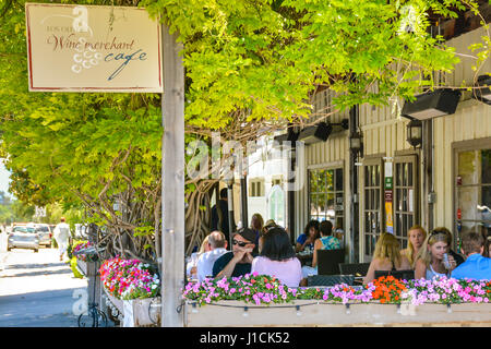 People enjoy the outdoor patio dining at the Los Olivos Wine merchant & Cafe in Los Olivos, CA surrounded by colorful - Stock Photo