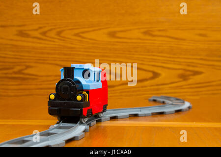 A toy train rides on rails - Stock Photo